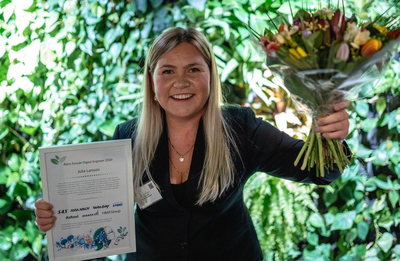 Julia Larsson, årets Female Digital Engineer, med blommor och diplom.