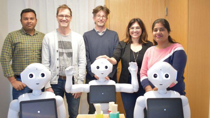 Forskargrupp vid Umeå universitet tilslammans med tre robotar Pepper.