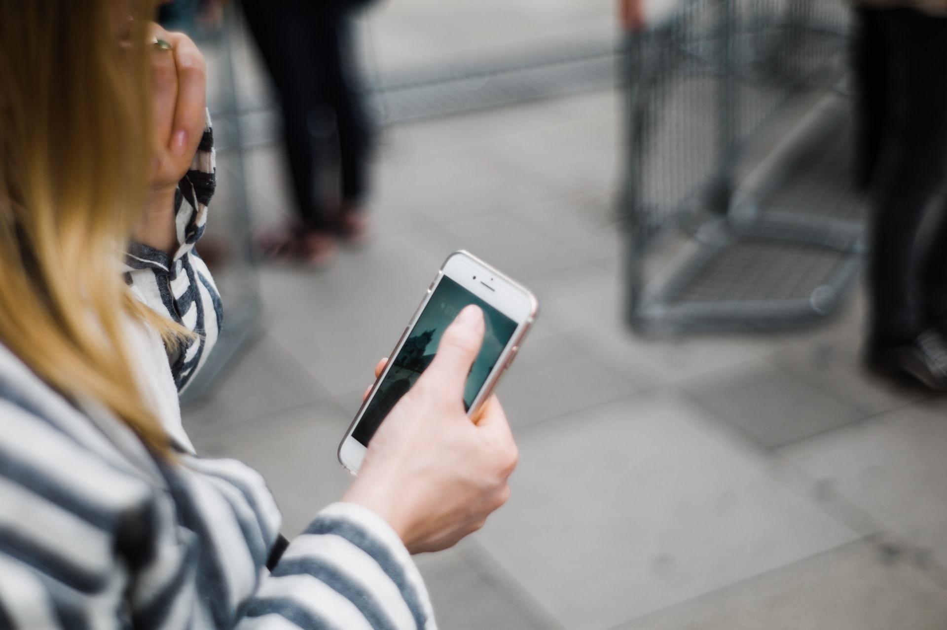Bilden visar en kvinnas hand som håller i sin mobiltelefon.