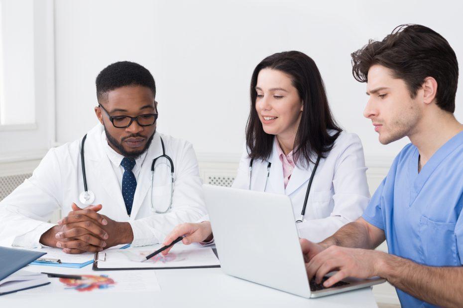 Bilden visar tre personer med medicinrock och medicinsk utrustning, en laptop samt en bok som sitter vid ett bord och samtalar.
